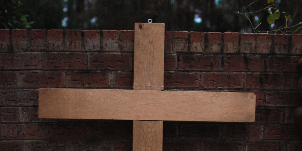 A cross on a brick wall.